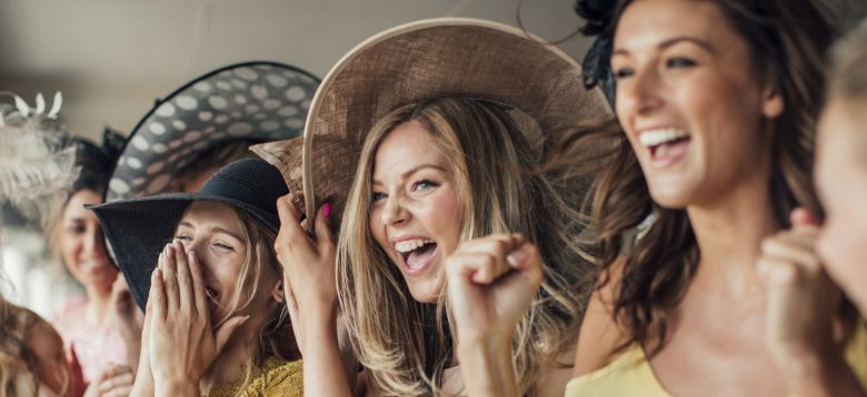 A group of young women cheering on for the running horses on ladies day.