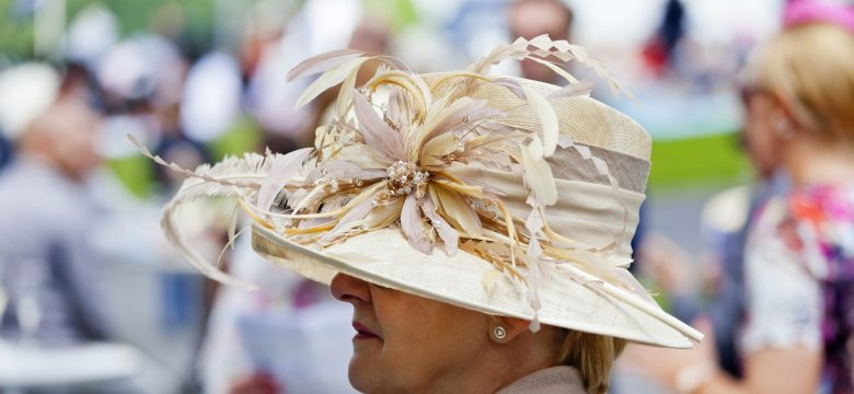 A stylish, mature lady with an elegant summer hat, at the racetrack at Chantilly on Ladies Day for the Prix Diane, enjoying a glass of champagne.