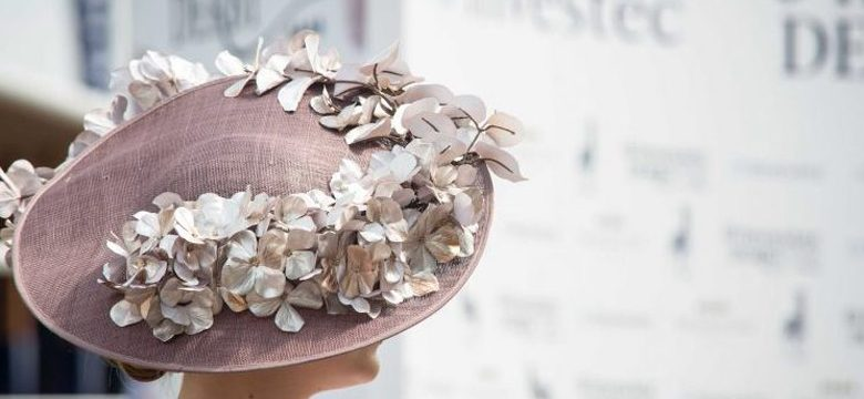 Elegant blush pink hat worn on tilted on the head, adorned with silk flowers. Lady enjoying the Epsom Derby